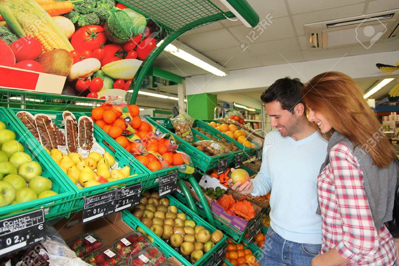 Couple at the supermarket doing grocery shopping Stock Photo - 9480404