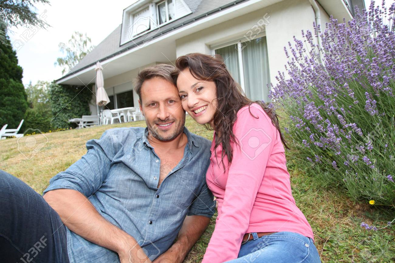 Portrait of happy couple sitting in front of their new house Stock Photo - 9910790