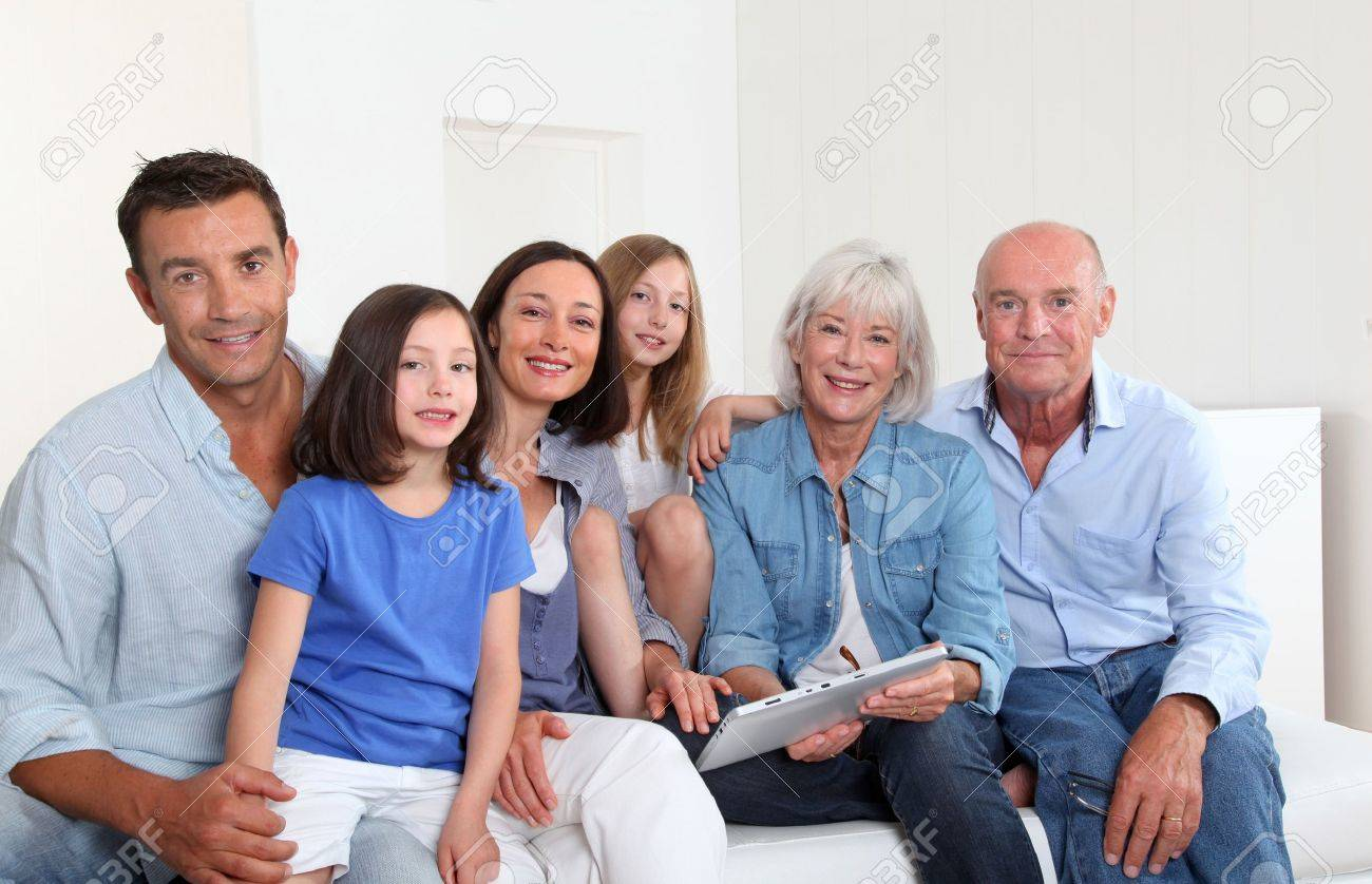 3-generation family sitting in couch with electronic tablet Stock Photo - 9903773