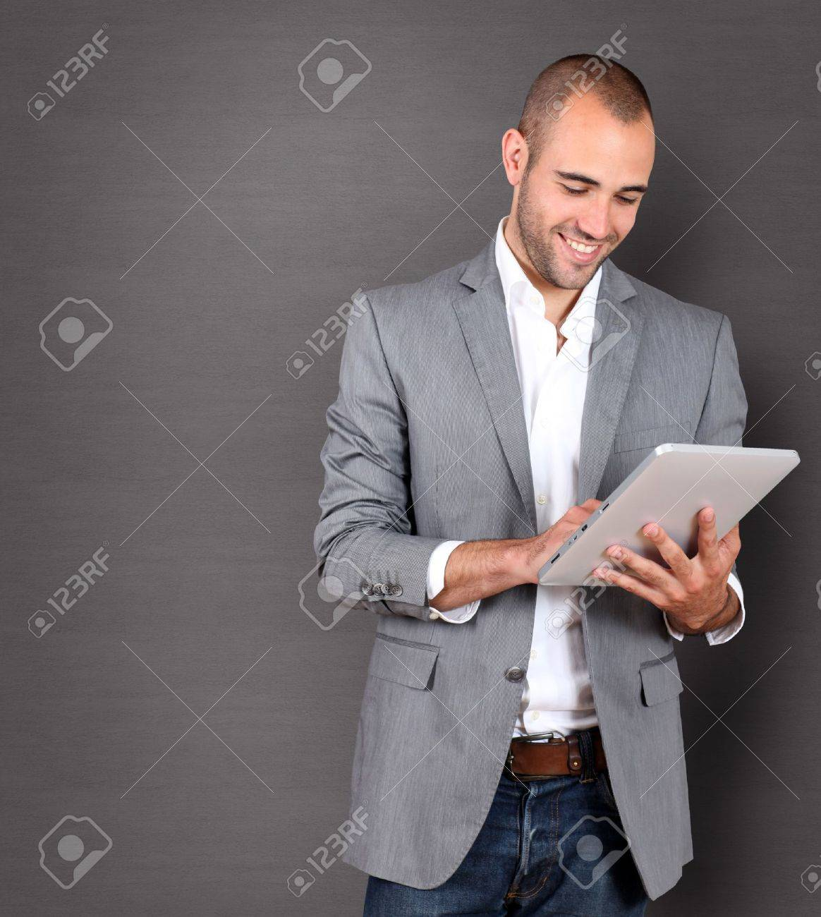 Cool businessman using touchpad on grey background Stock Photo - 10013374