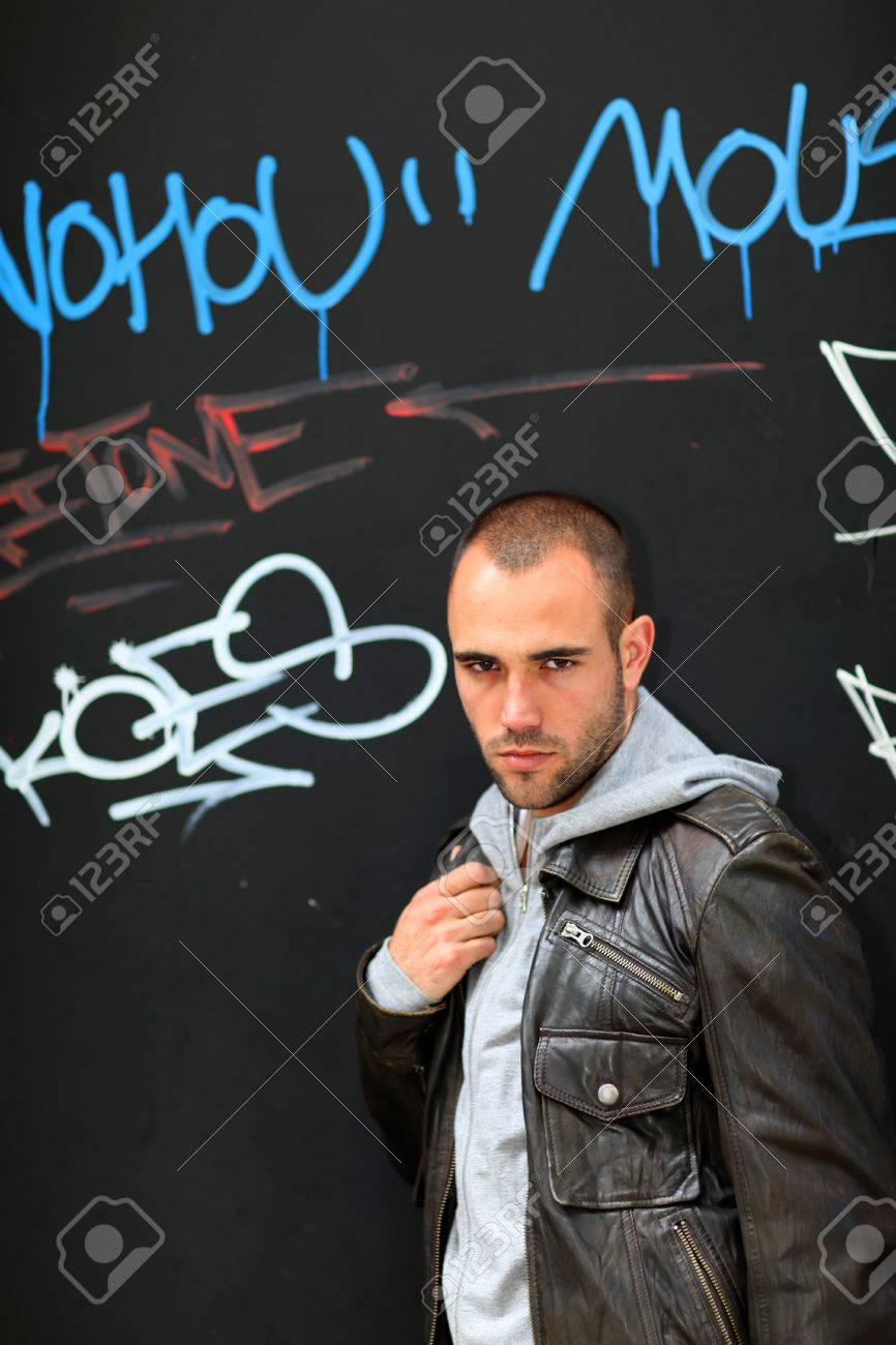 Portrait of bad boy standing on tagged wall Stock Photo - 10013724