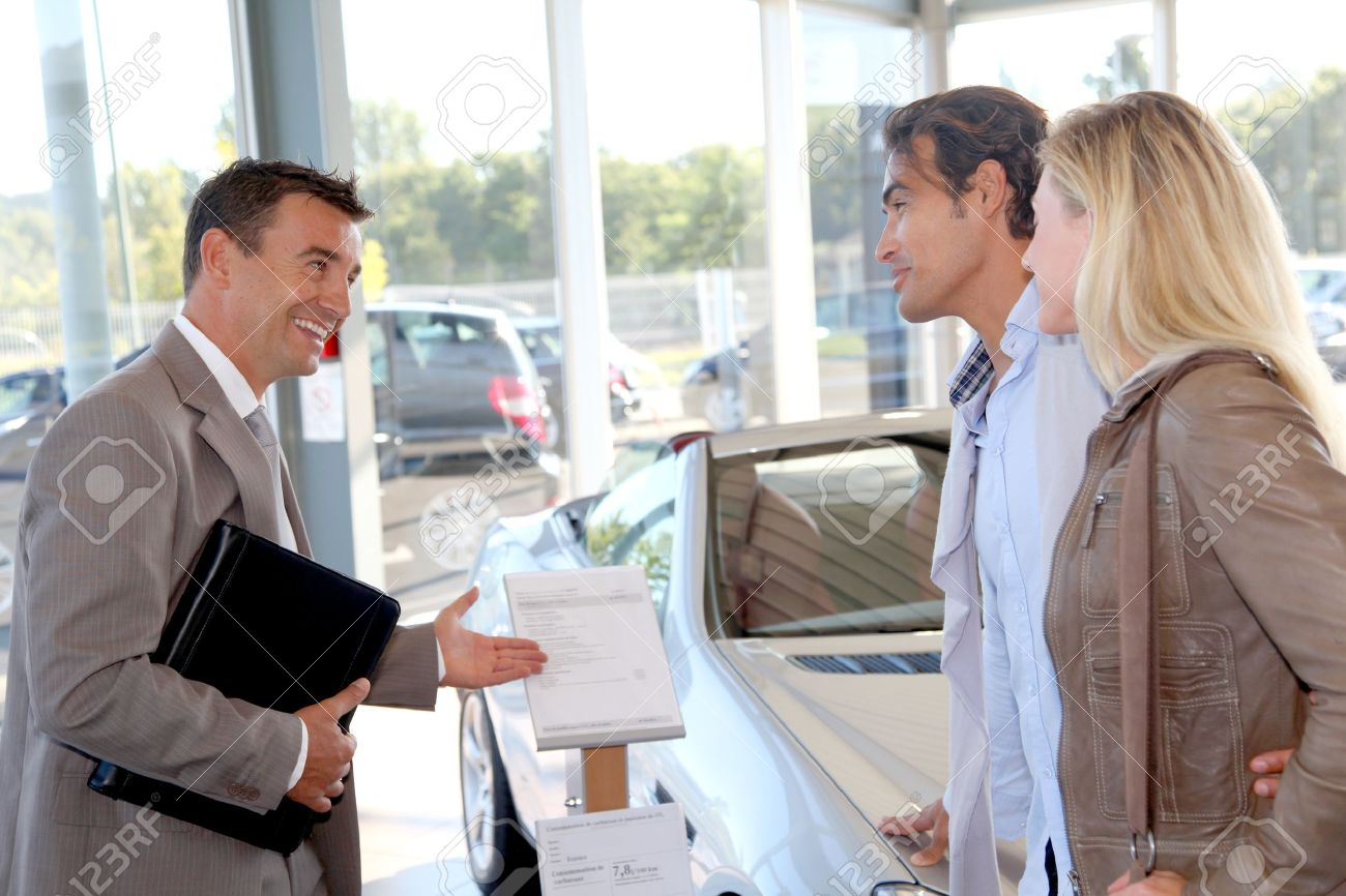 Car seller with couple in car dealership Stock Photo - 10624638