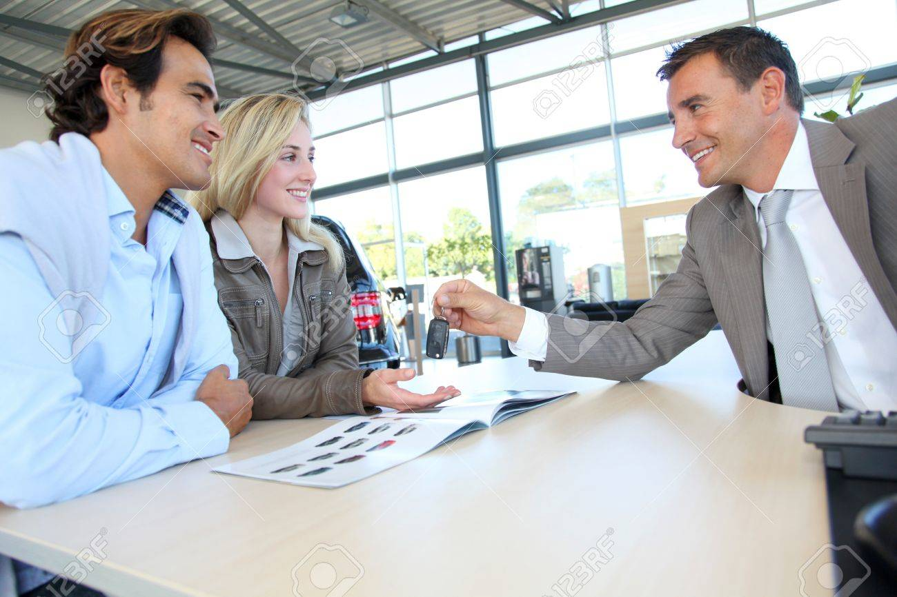 Car seller giving car key to buyers Stock Photo - 10624834
