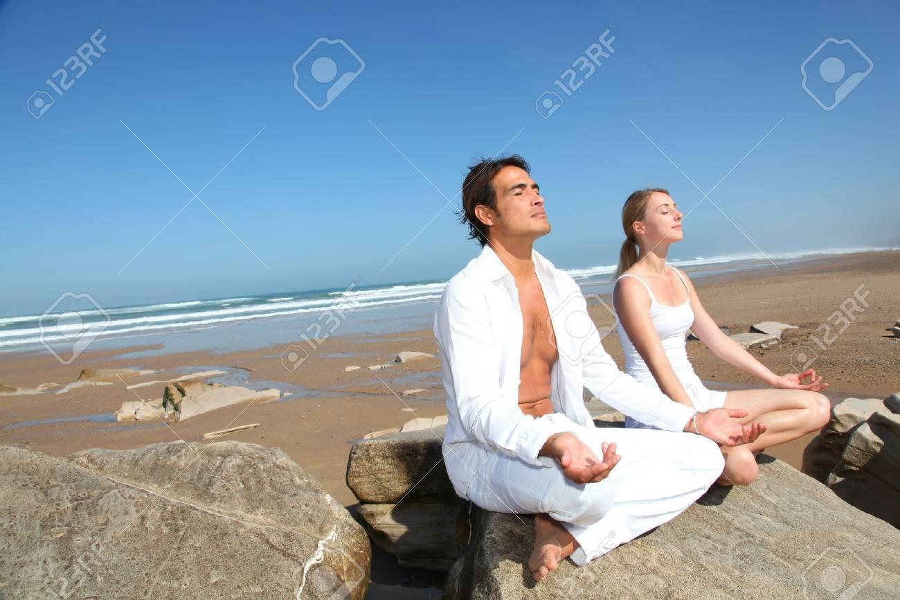 Couple doing yoga exercises on the beach Stock Photo - 10626468