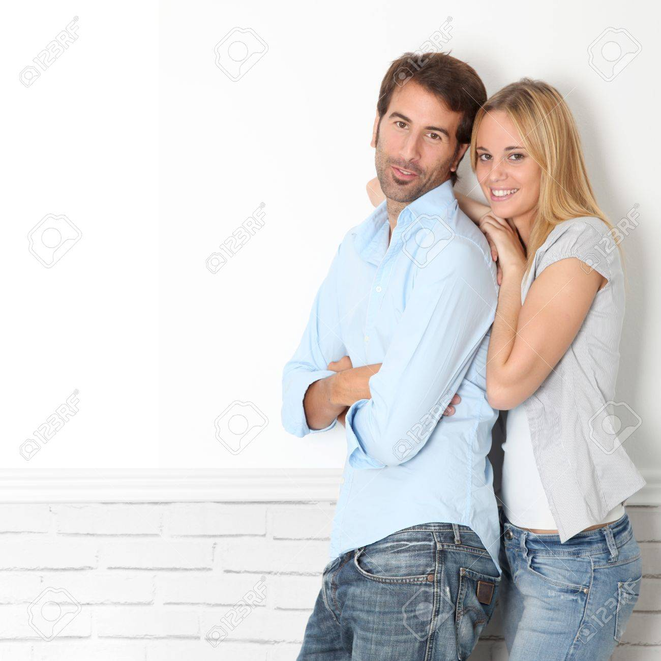 Young couple standing on white wall Stock Photo - 10797889