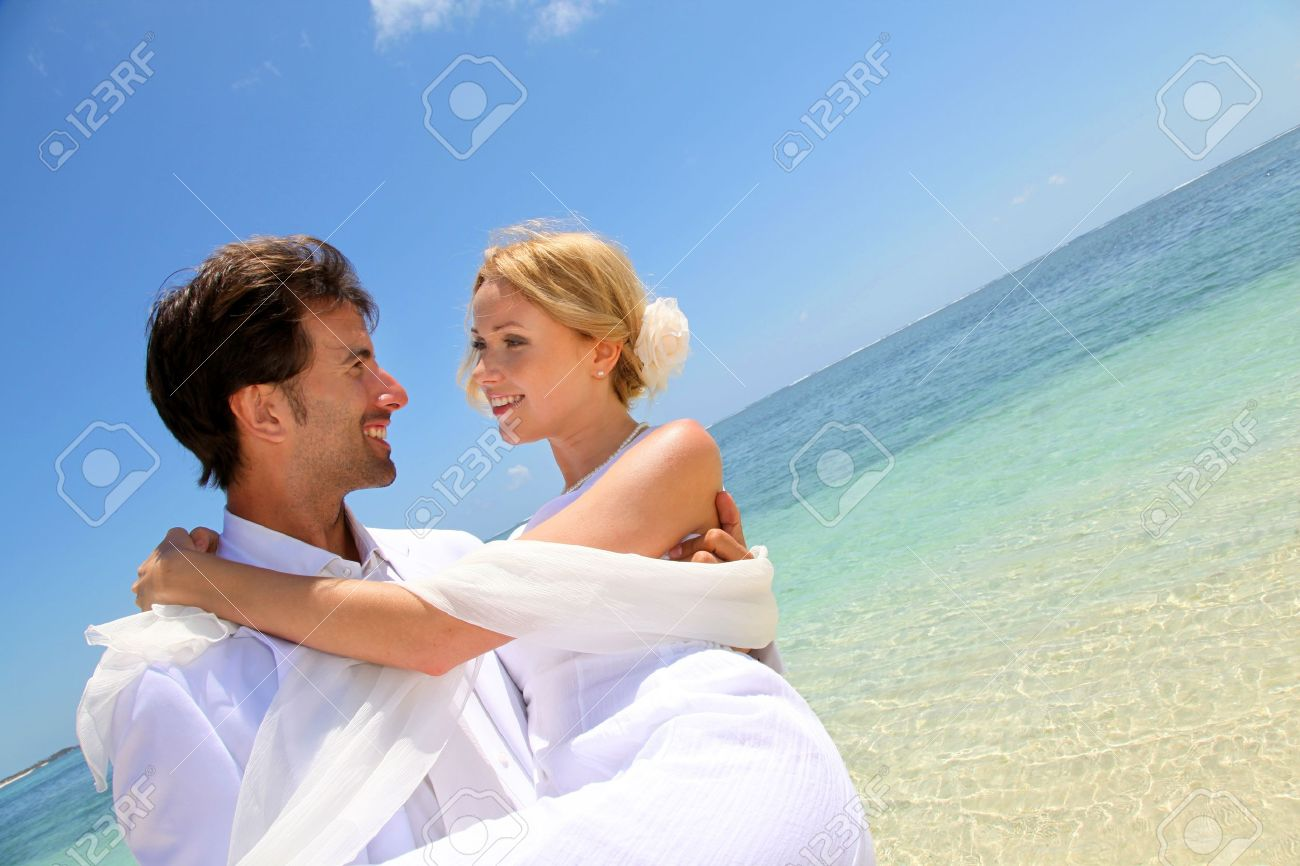 Groom holding bride in his arms by the sea Stock Photo - 11503638