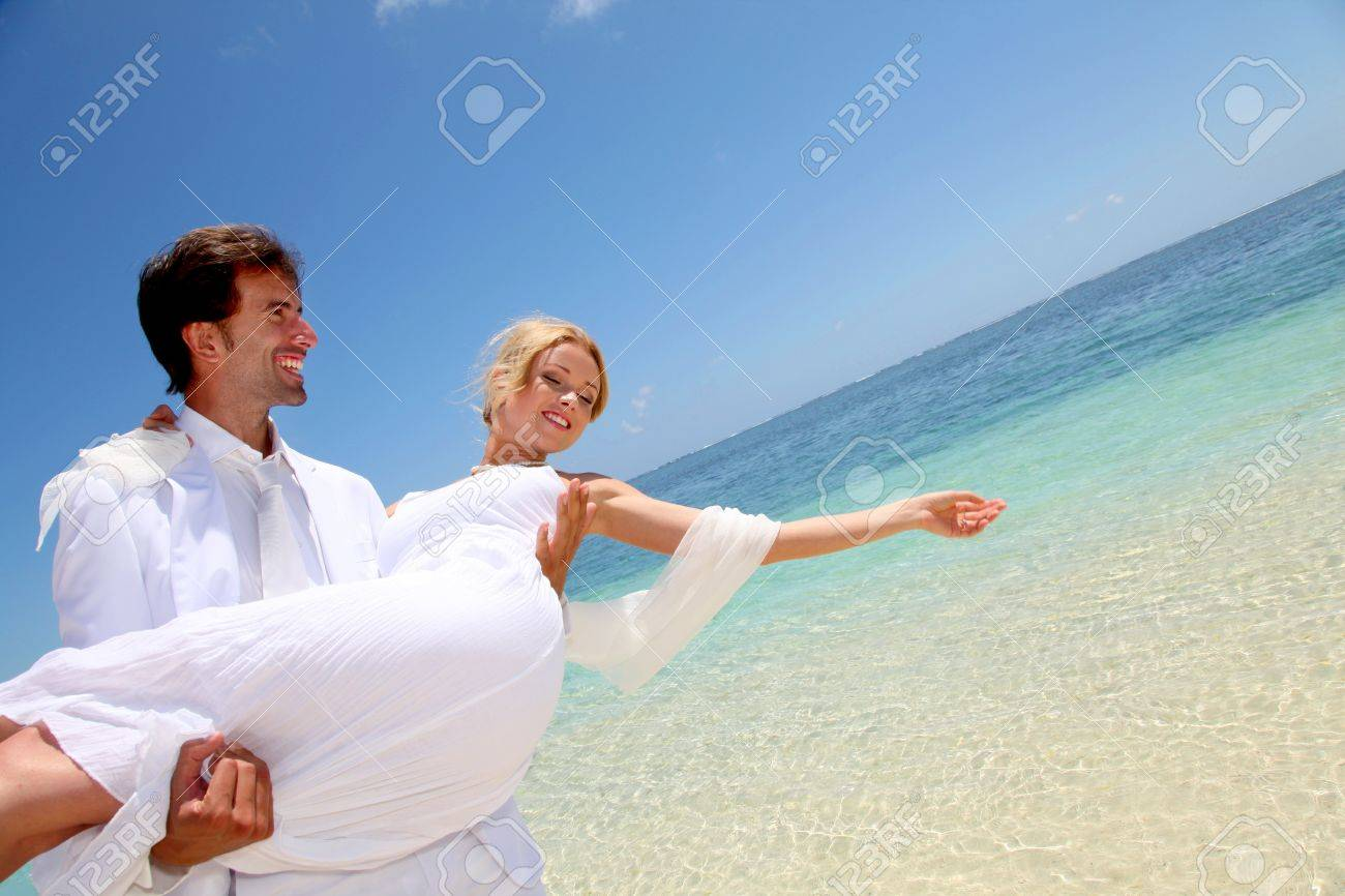 Groom holding bride in his arms by the sea Stock Photo - 11503709
