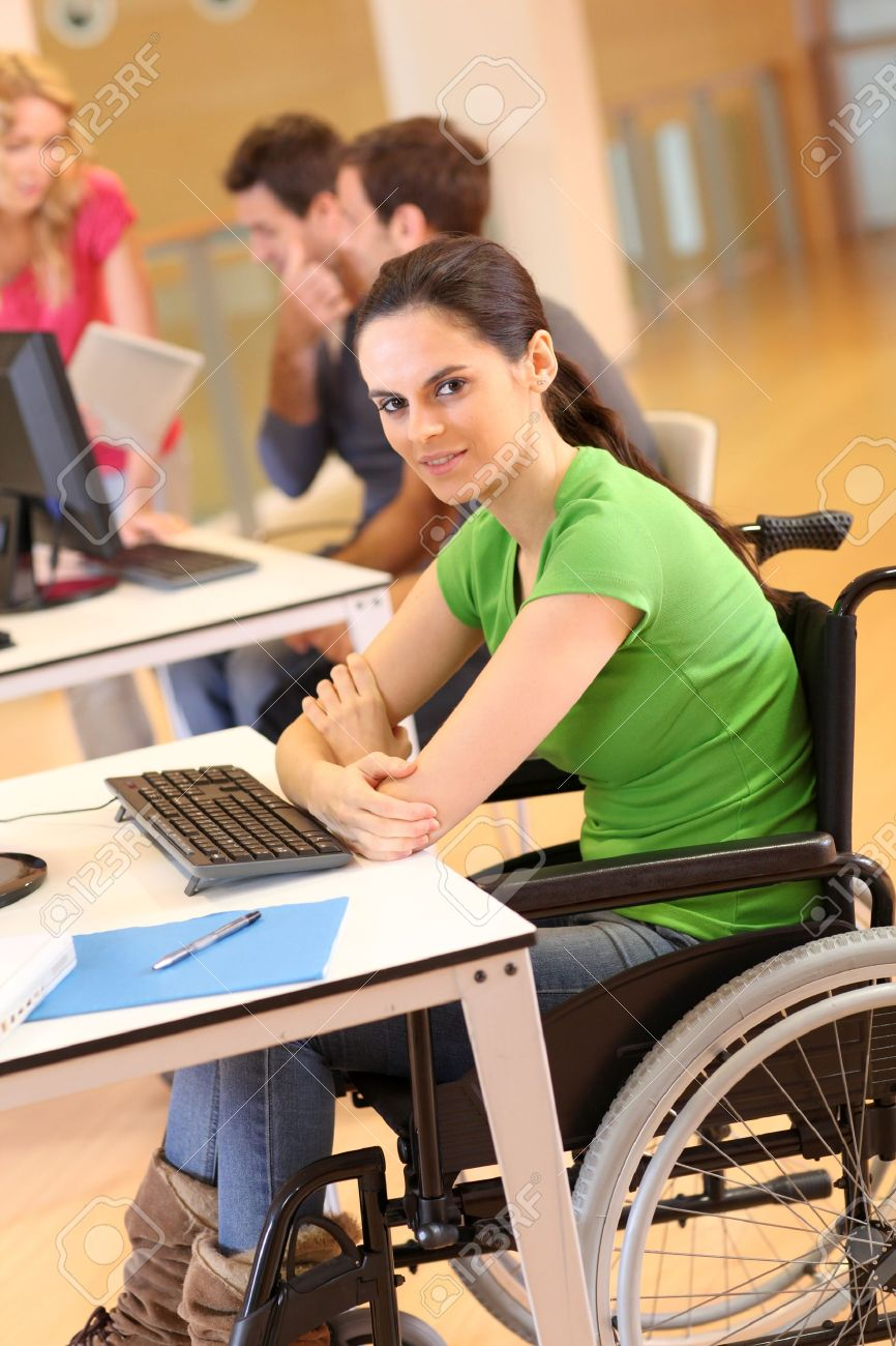 Young woman in wheelchair working in office Stock Photo - 12557064