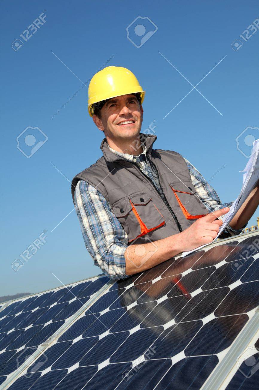 Man standing by solar panels with construction plan Stock Photo - 12556658