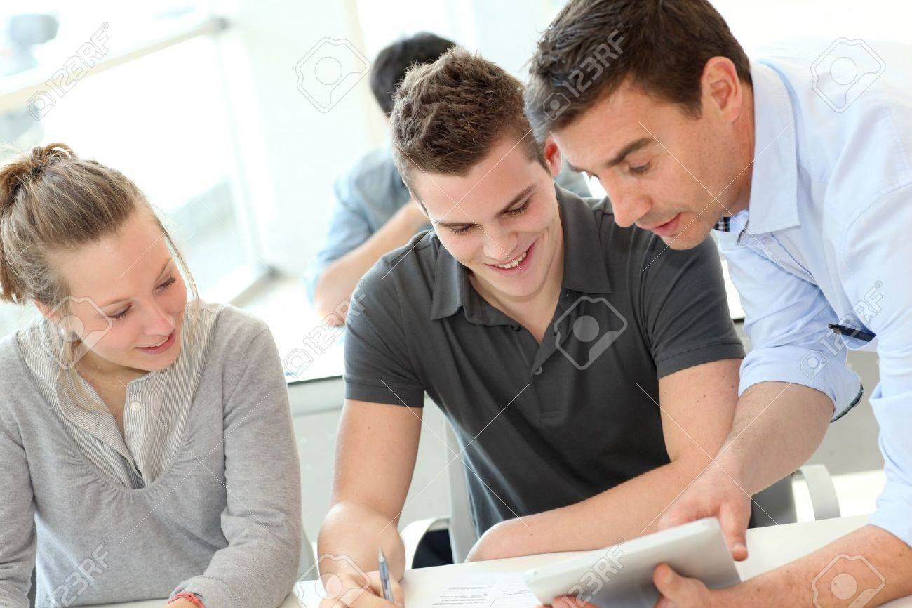 Teacher helping students with assignment Stock Photo - 12556702