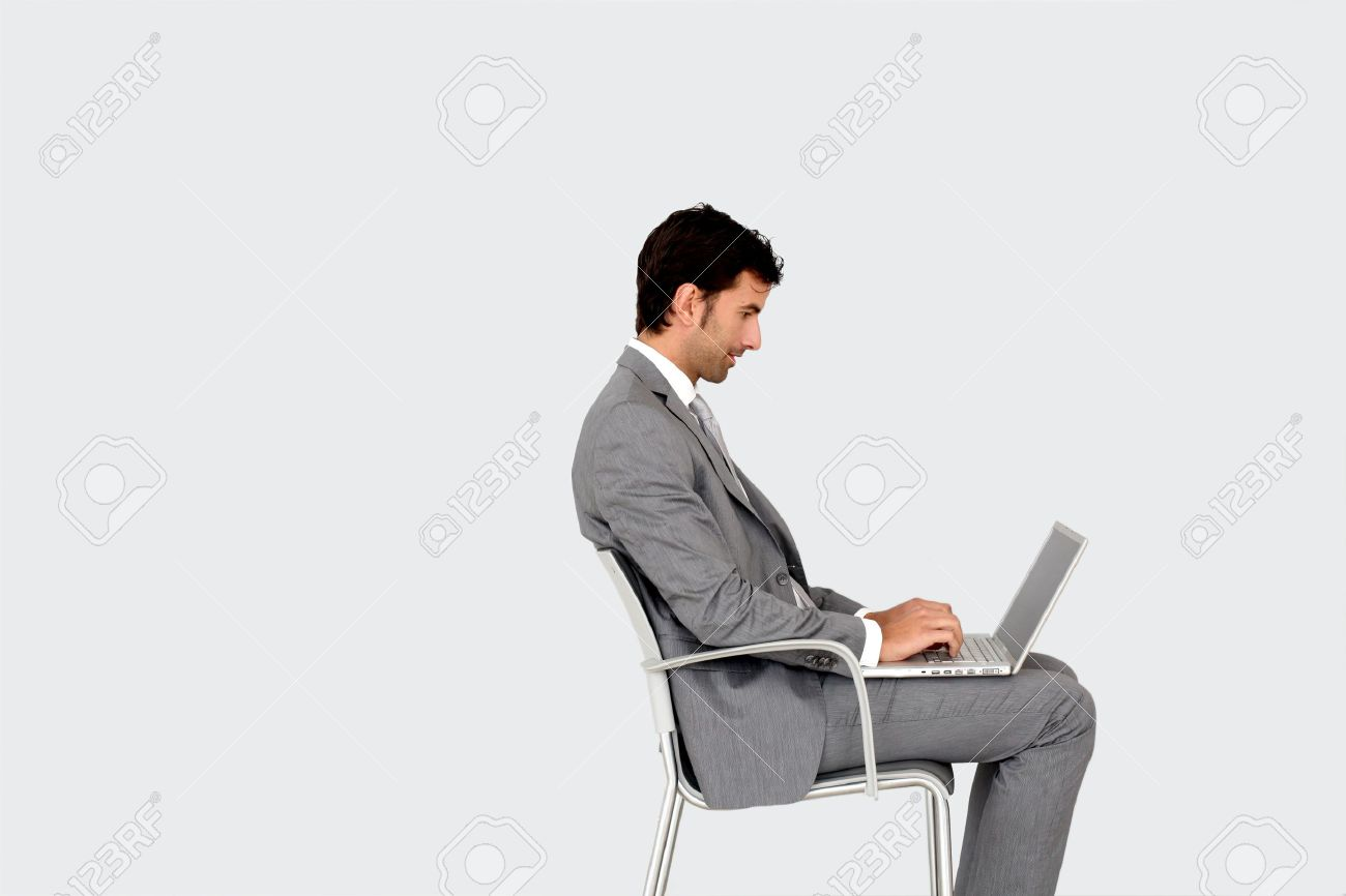 Man sitting in chair side - Businessman Sitting On Chair In Front Of Laptop Stock Photo 13262949