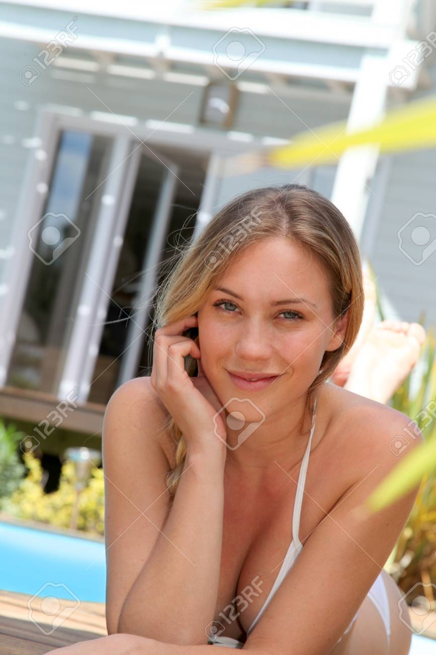 Portrait of beautiful blond woman relaxing by pool Stock Photo - 13764591