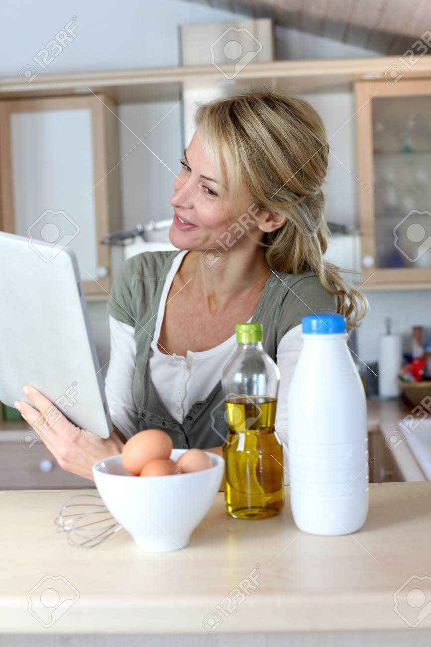 Woman in kitchen looking at dessert recipe on internet Stock Photo - 13904706