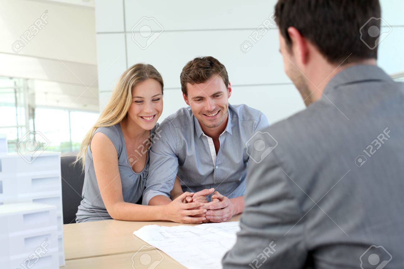 Couple in real-estate agency talking to construction planner Stock Photo - 13904599