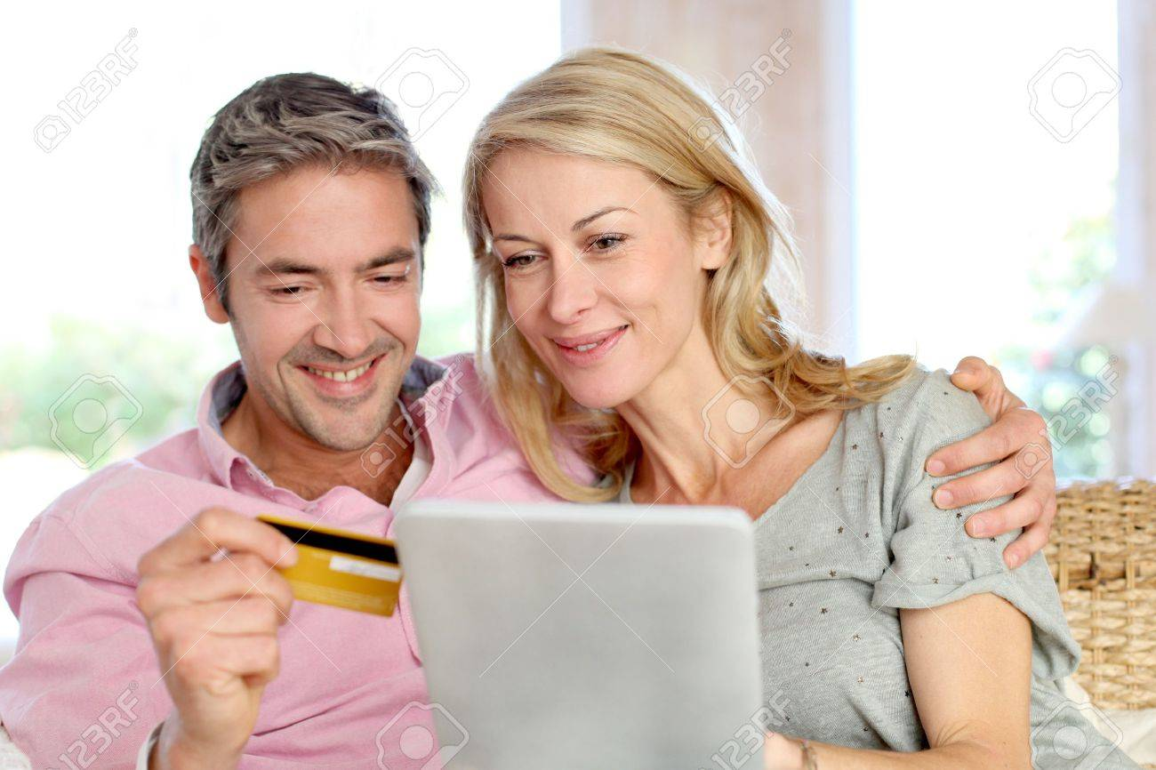 Couple sitting in sofa at home and doing online shopping Stock Photo - 13948672