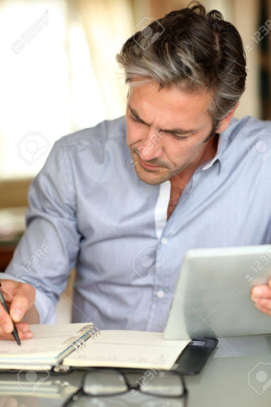 Handsome guy working from home with electronic tablet Stock Photo - 13948785