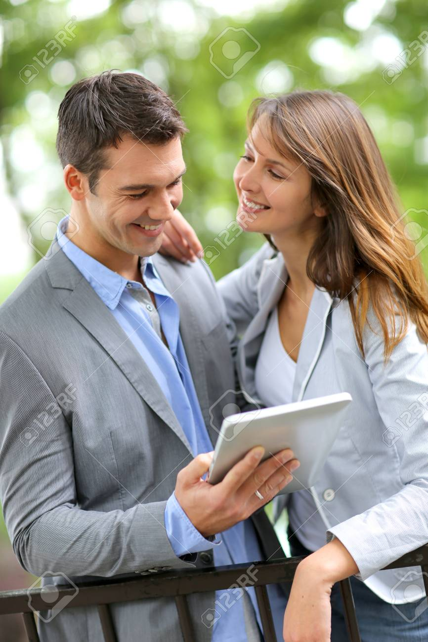 Couple standing in park with electronic tablet Stock Photo - 14663835