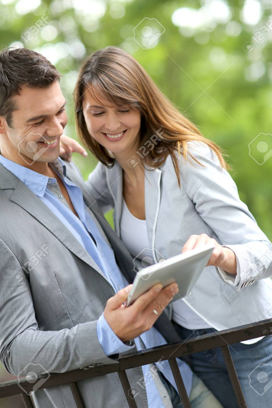 Couple standing in park with electronic tablet Stock Photo - 14663829