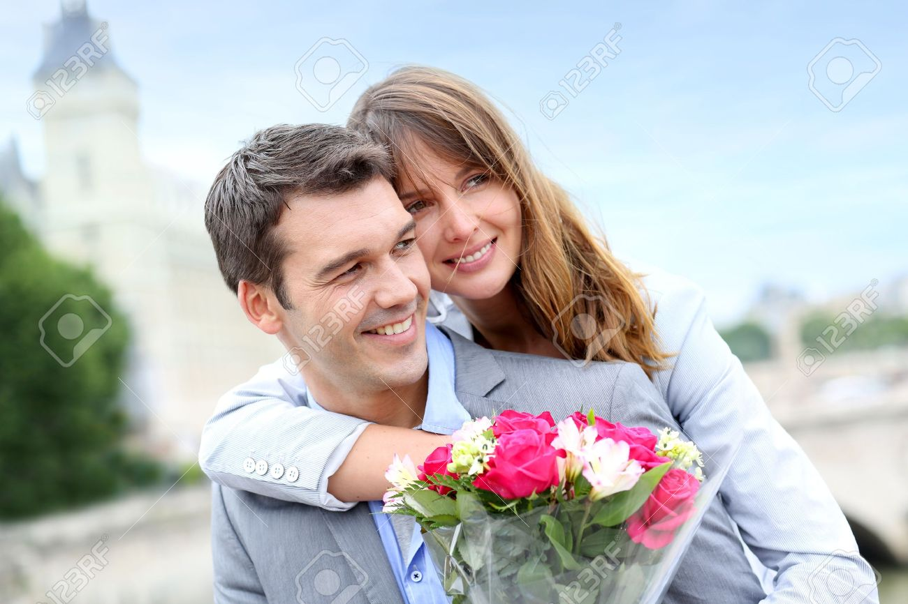 Portrait of romantic man giving flowers to woman Stock Photo - 14679453