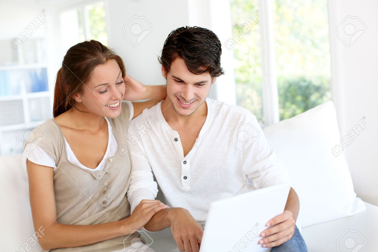 Happy young couple using laptop computer at home Stock Photo - 15278159