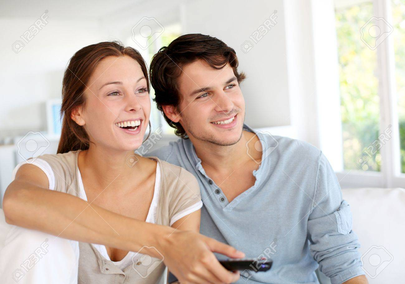 Couple sitting in sofa with remote control in hands - 15279248