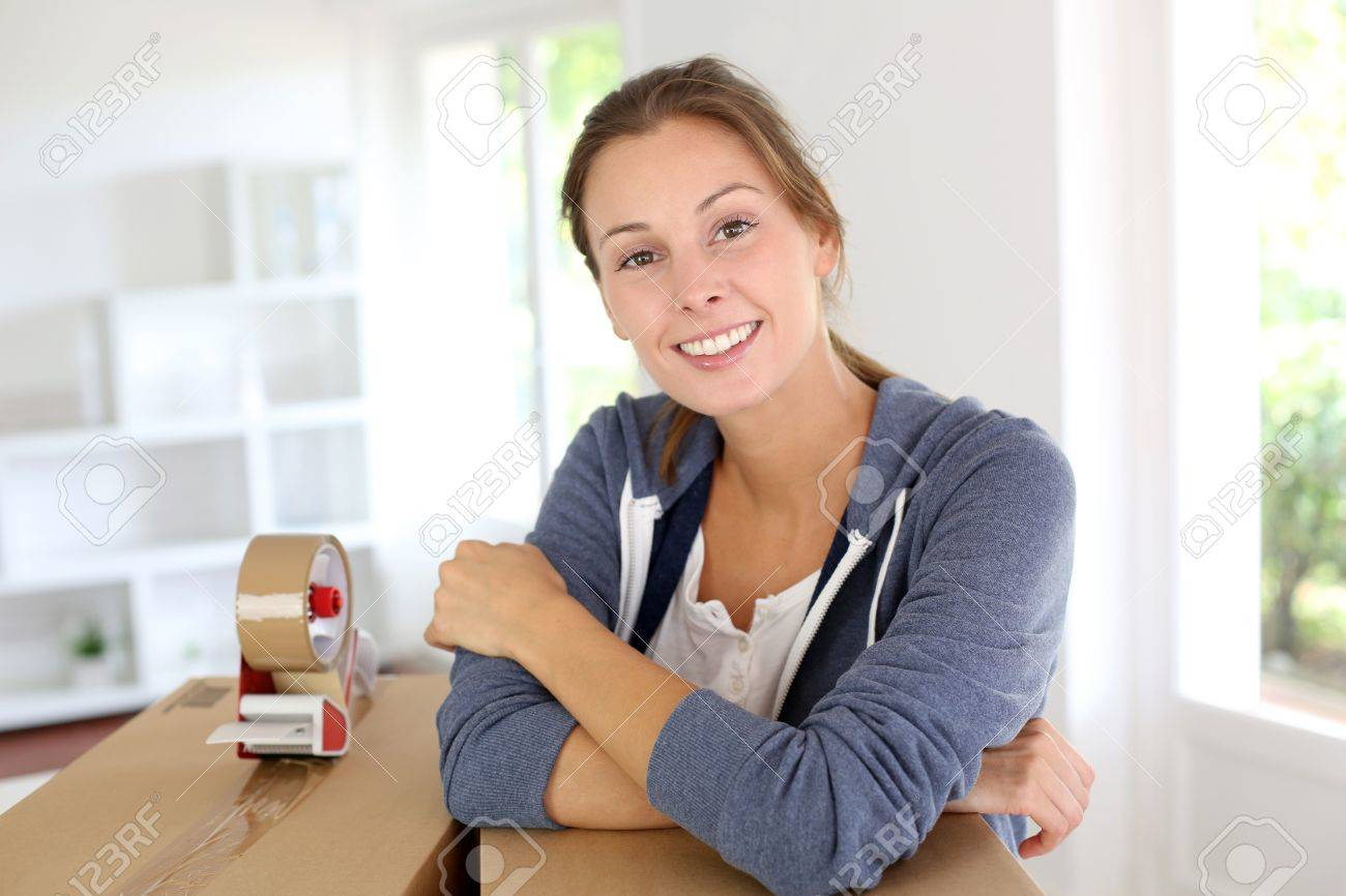 Smiling young woman packing boxes to move out Stock Photo - 15279253