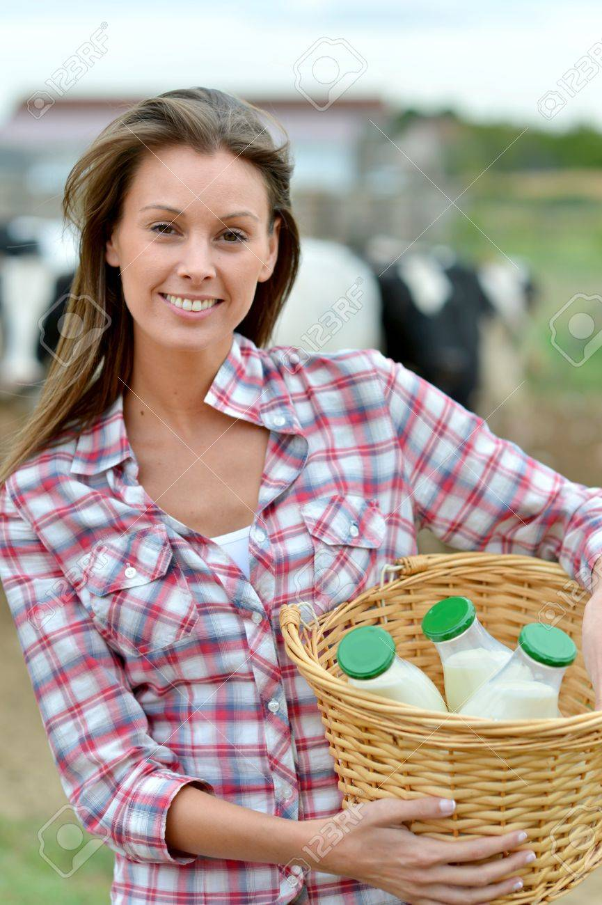 Smiling young farmer carrying bottles of fresh milk Stock Photo - 15427783