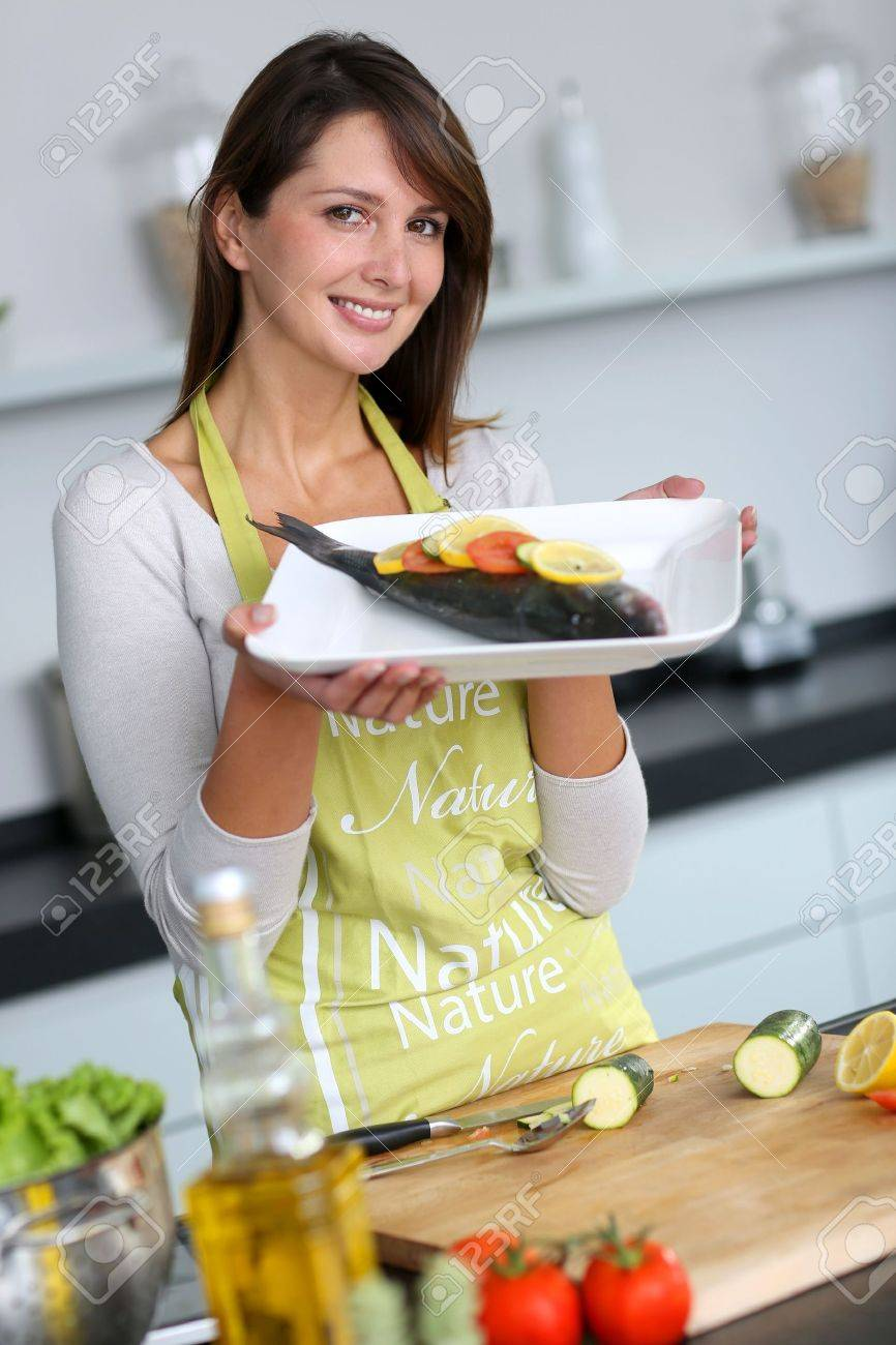 Woman in kitchen holding fish dish Stock Photo - 15831983