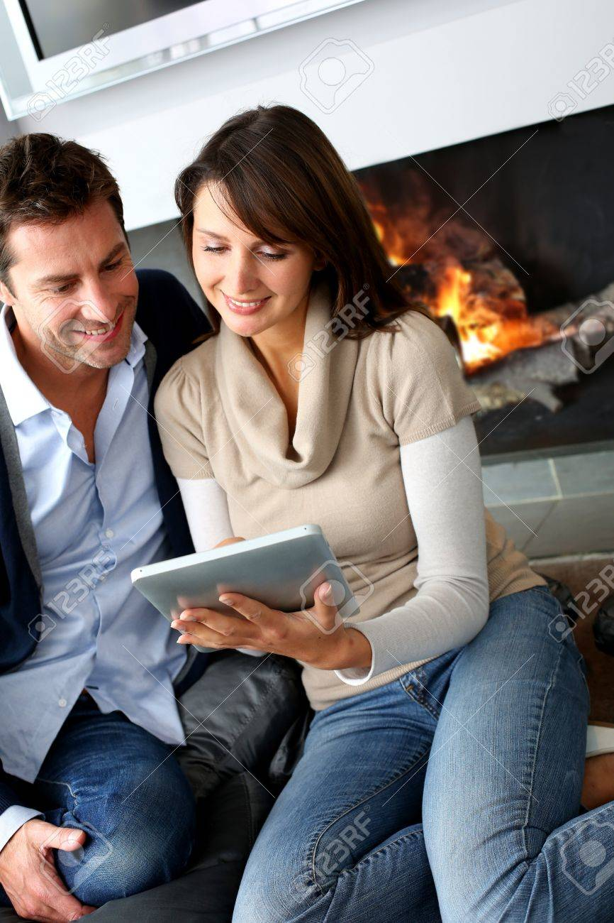 Couple sitting by fireplace and websurfing with tablet Stock Photo - 15832034