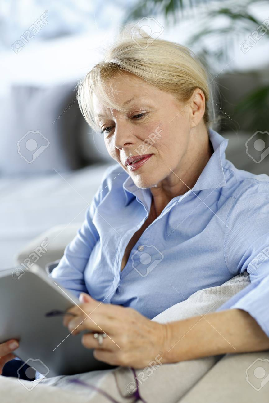 Senior woman using electronic tablet in sofa Stock Photo - 16398499
