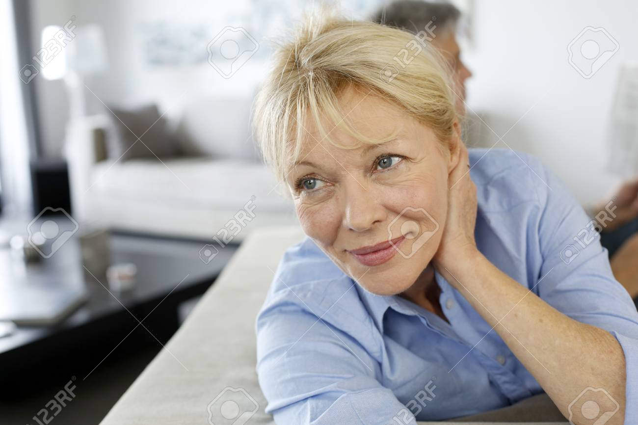 Senior woman sitting in couch, husband in background Stock Photo - 16397662