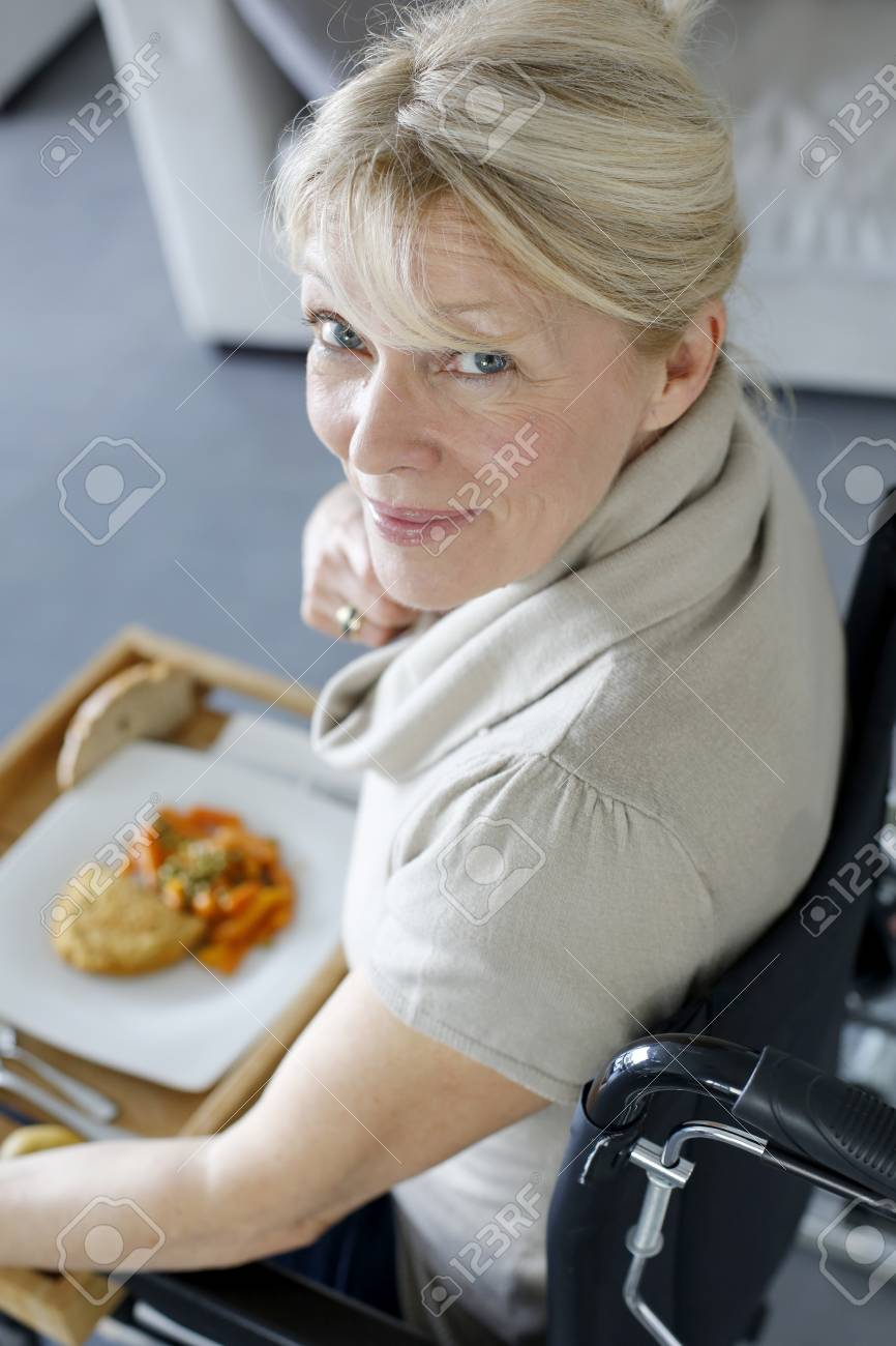 Senior woman in wheelchair holding lunch tray Stock Photo - 16398522