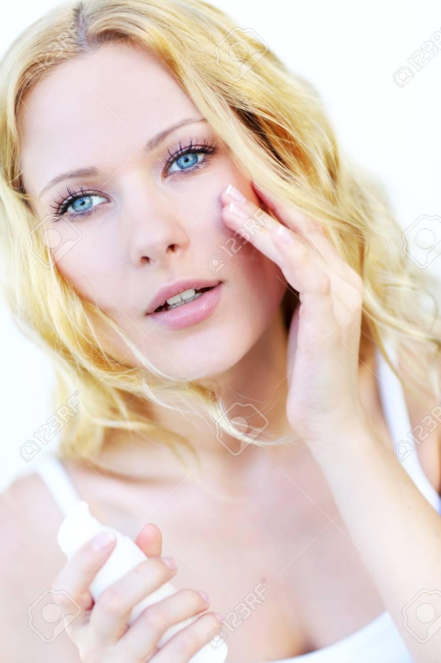Portrait of beautiful woman applying moisturizer Stock Photo - 16949361