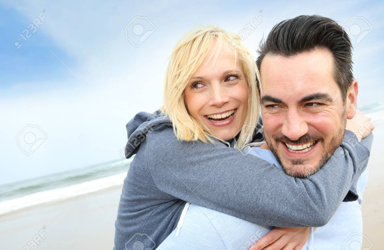 Cheerful couple standing on the beach Stock Photo - 18919072