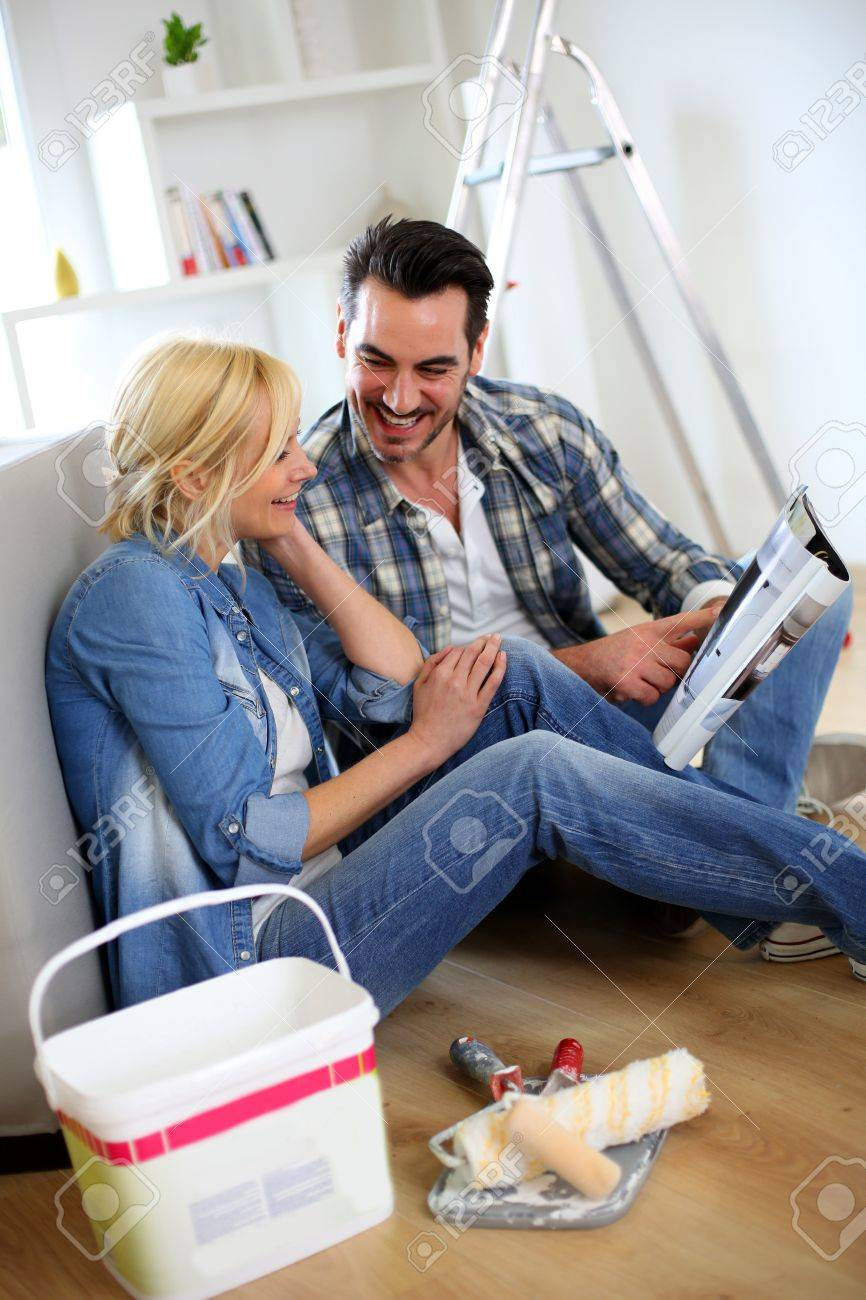 Couple sitting on the floor choosing paint colour Stock Photo - 18939460