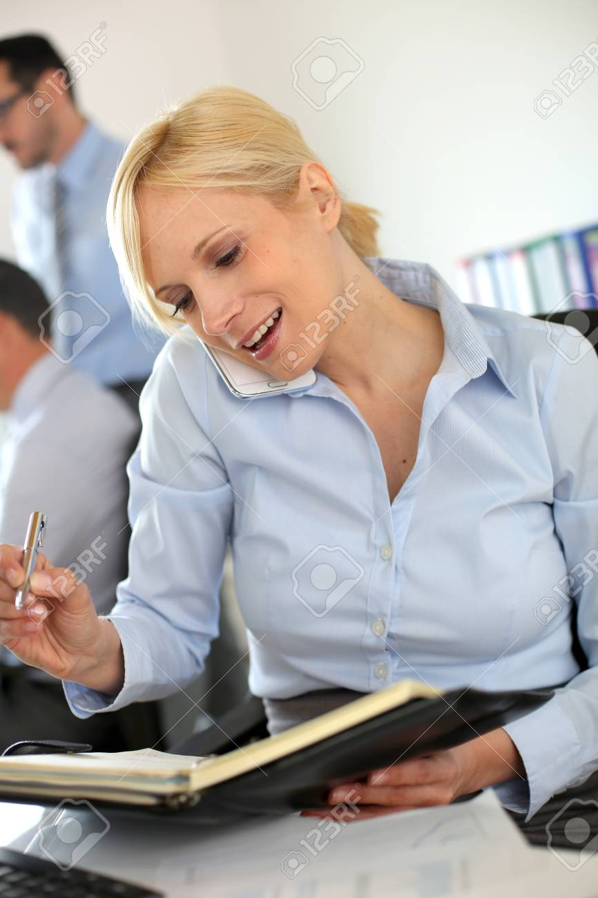 Businesswoman on the phone writing on agenda Stock Photo - 18941706