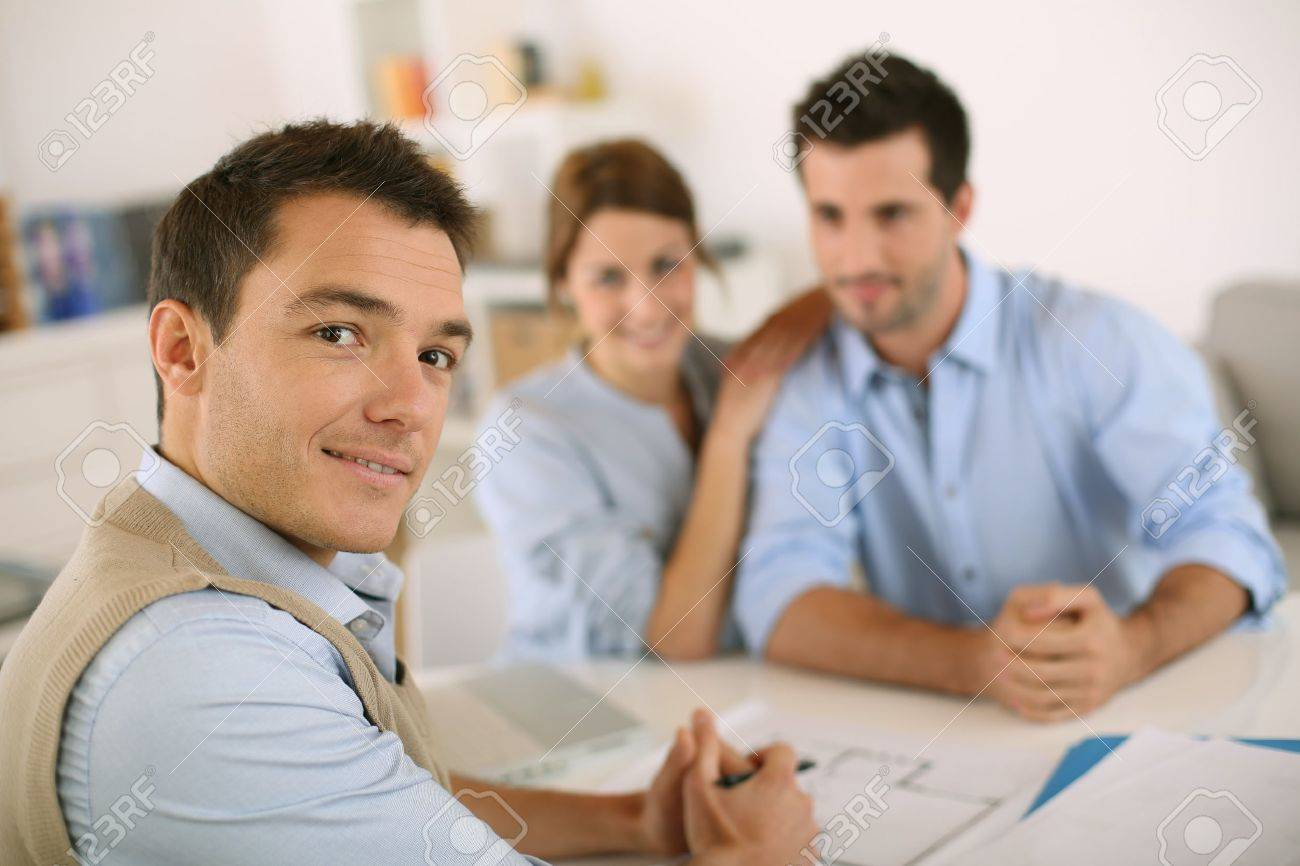 Smiling Financial Adviser With Young Couple Stock Photo, Picture ...