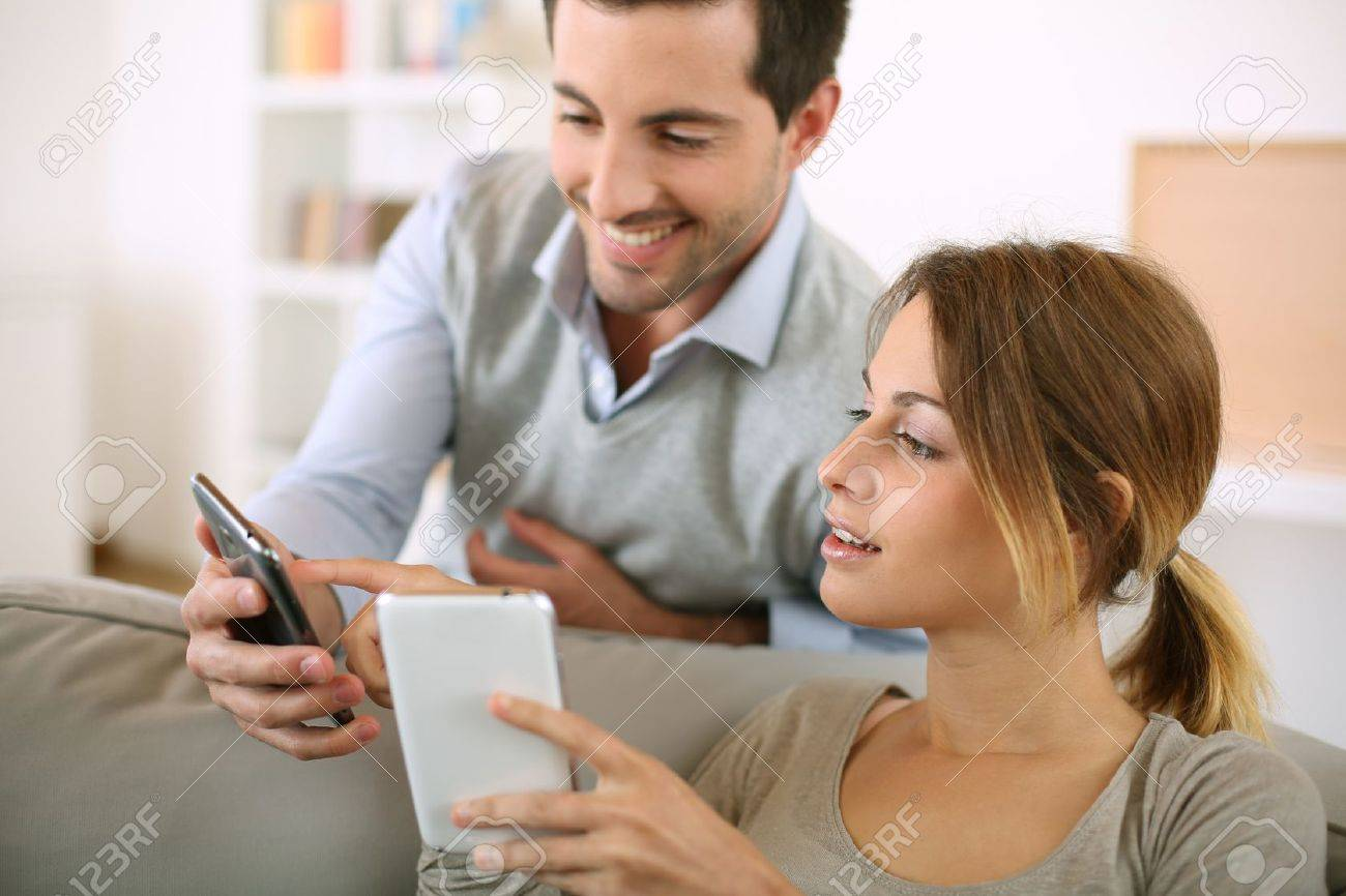 Young couple using smartphone at home Stock Photo - 20190063