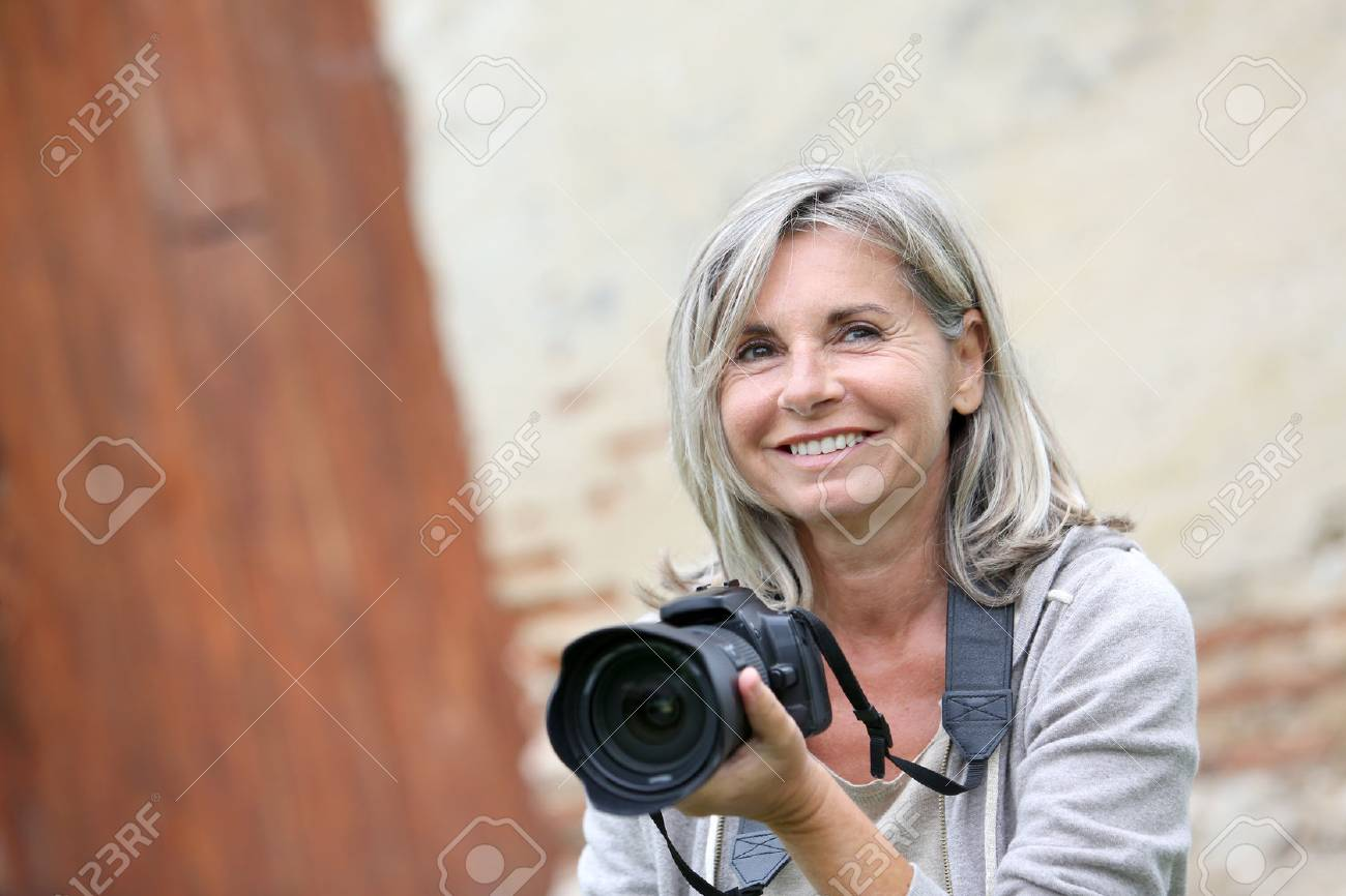 Portrait Of Mature Woman Shooting With Photo Camera Stock Photo