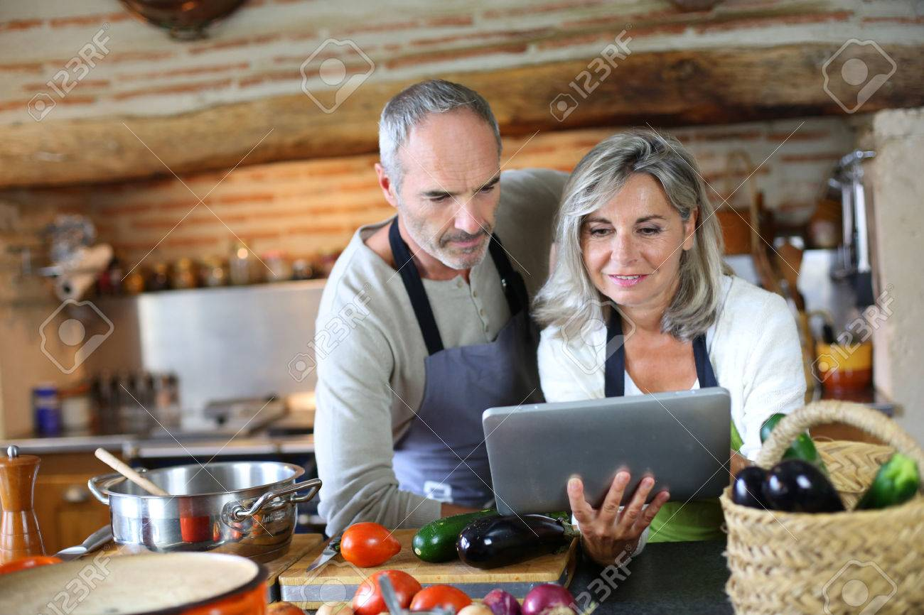 Home Kitchen Cooking Senior Couple In Home Kitchen Looking At Tablet Stock Photo