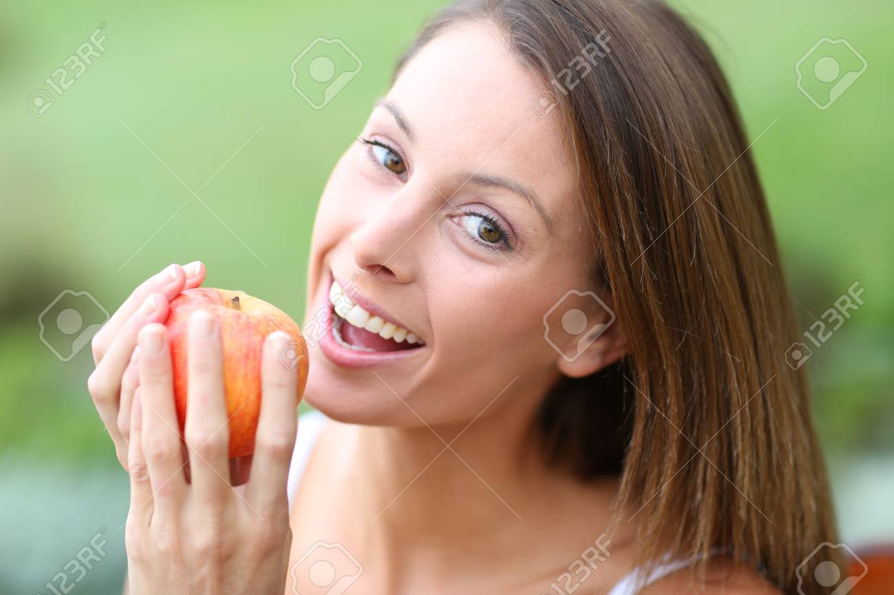 Beautiful girl eating red apple Stock Photo - 22439330