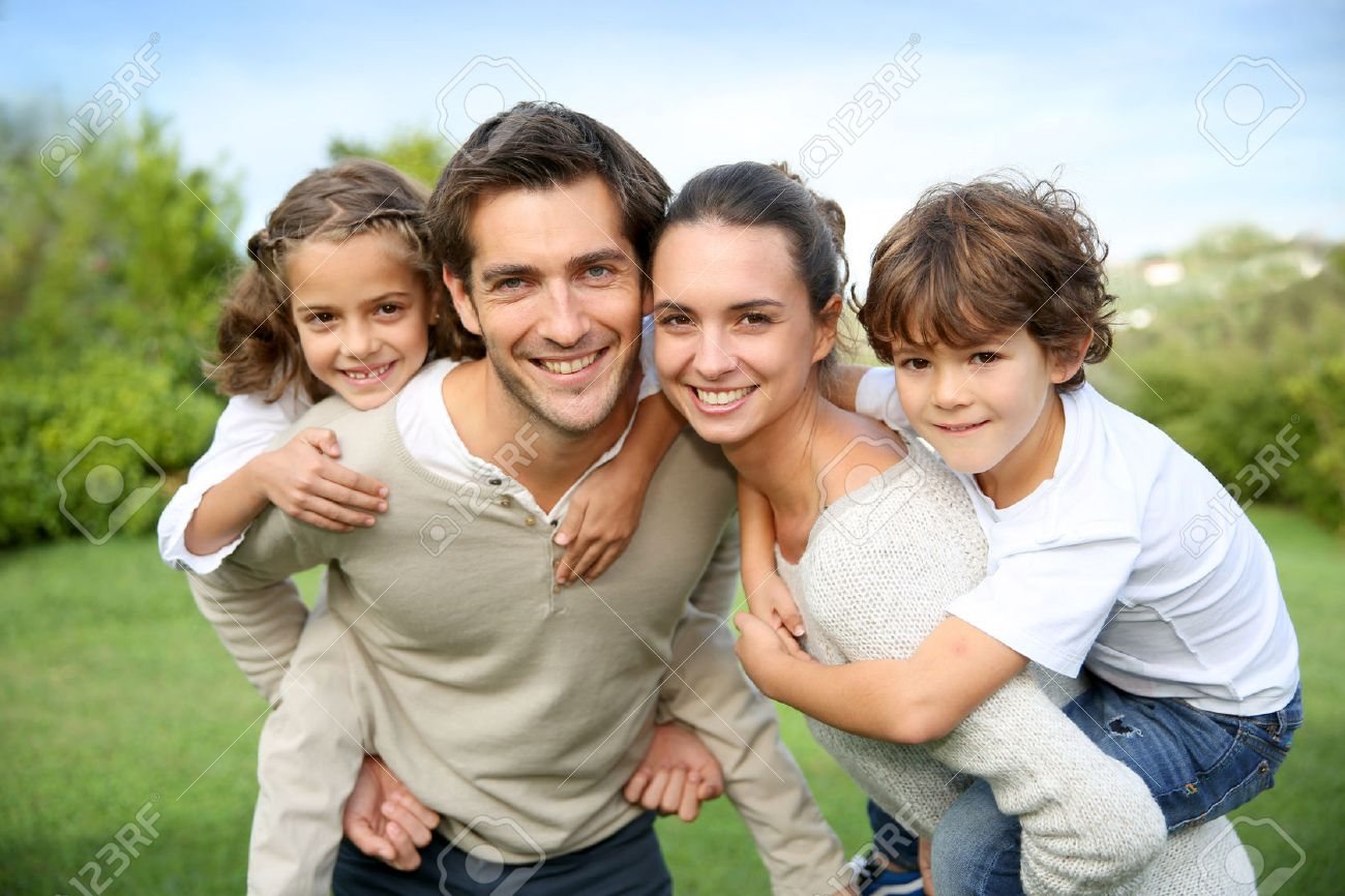 Parents giving piggyback ride to children Stock Photo - 23365236
