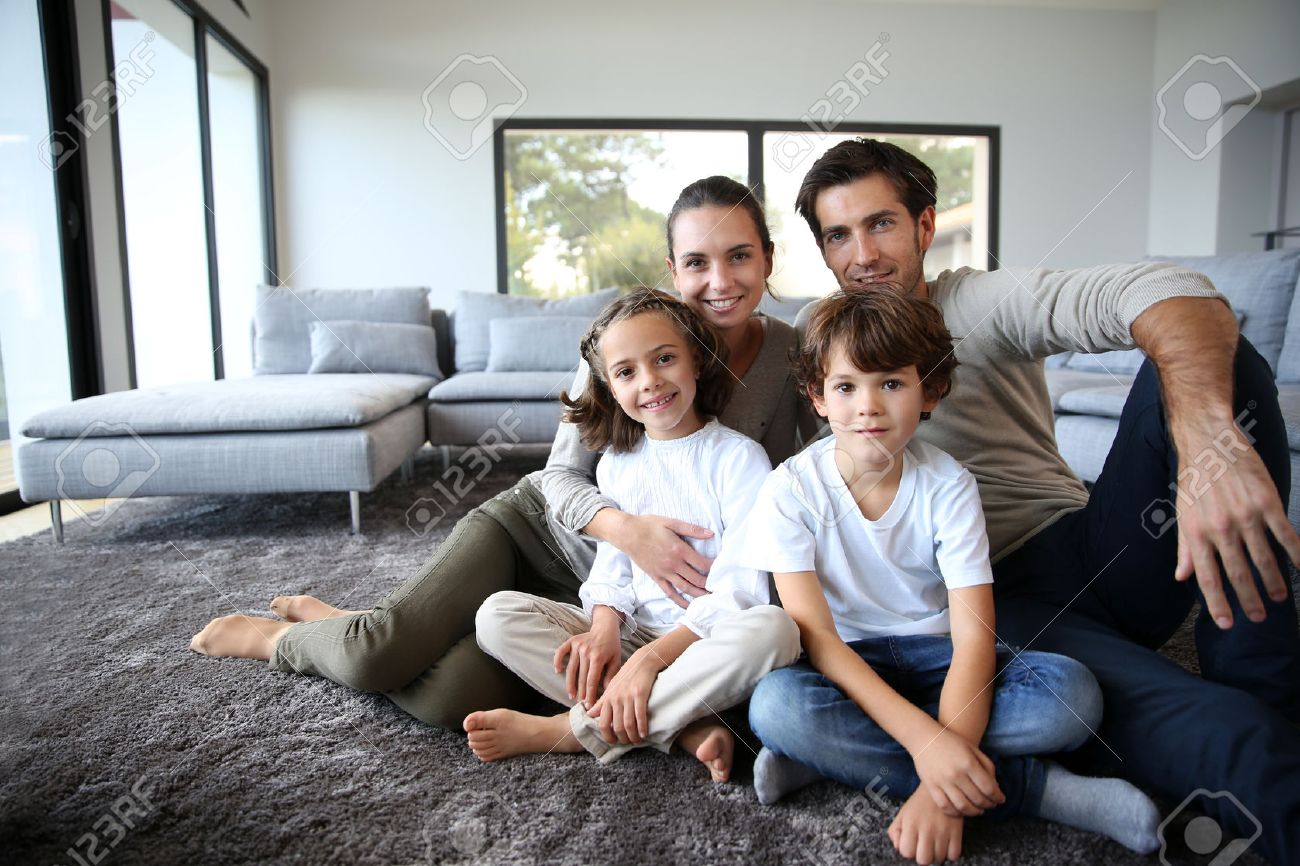 Happy family portrait at home sitting on carpet Stock Photo - 23365183