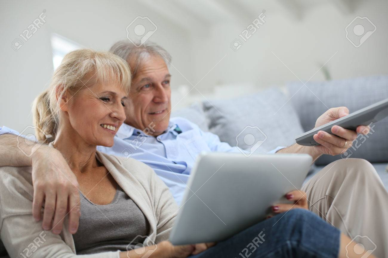 Senior couple sitting in sofa and watching tv - 30220993