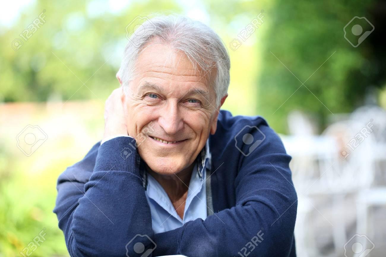 Portrait of senior man sitting in home garden - 31780453