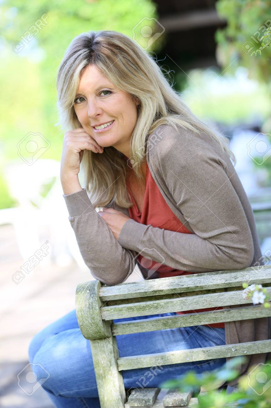 mature blond woman relaxing in outdoor bench stock photo, picture