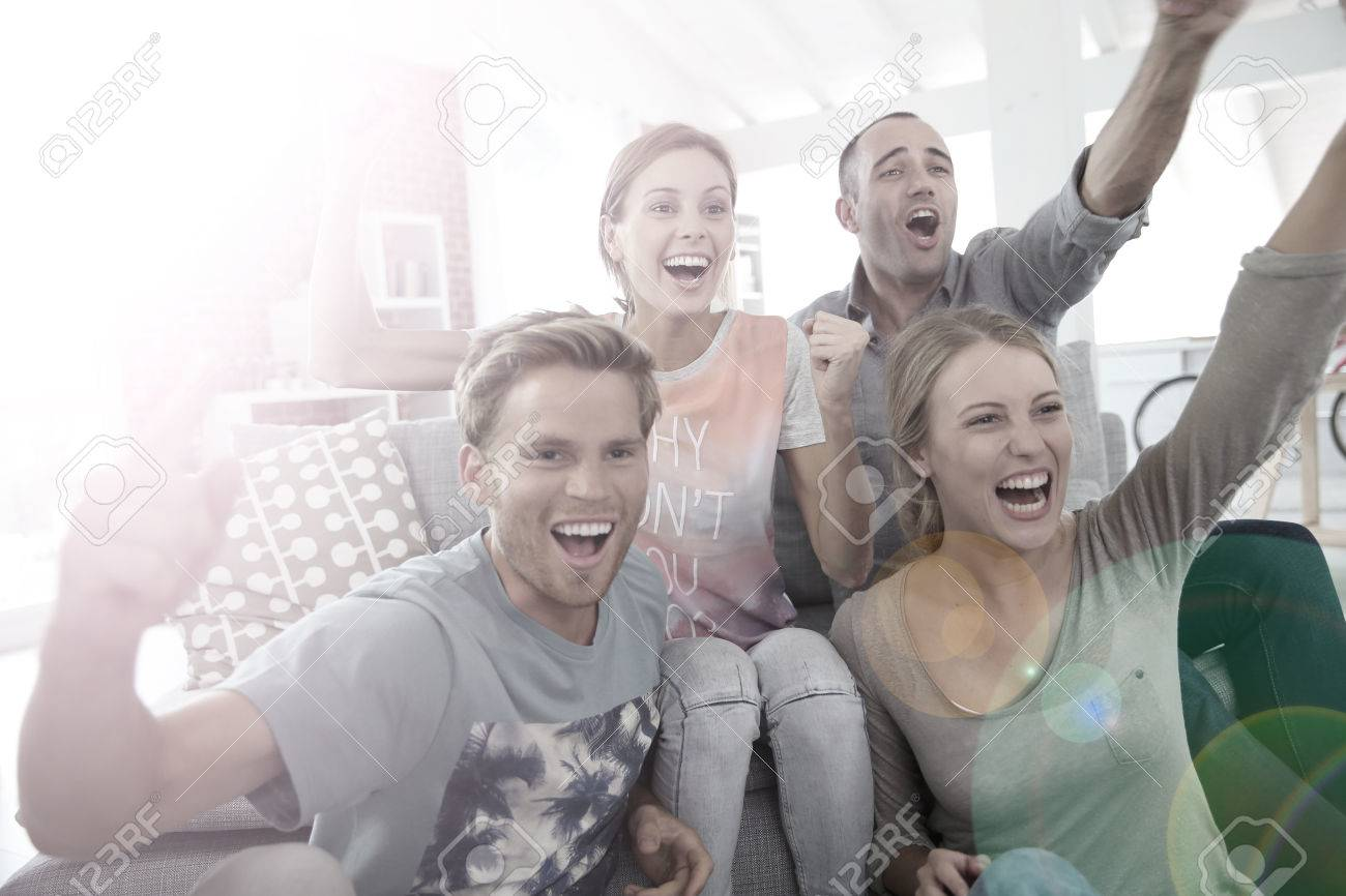 Roommates in apartment watching football game - 35458335
