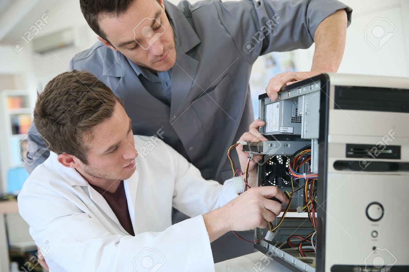 Young Adults Fixing Computer Hardware In Technology School Stock ...