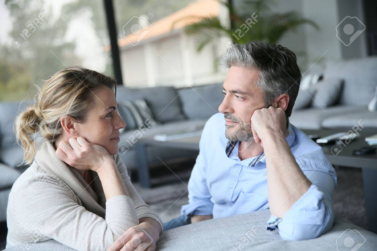 mature couple talking to each other in sofa stock photo picture and