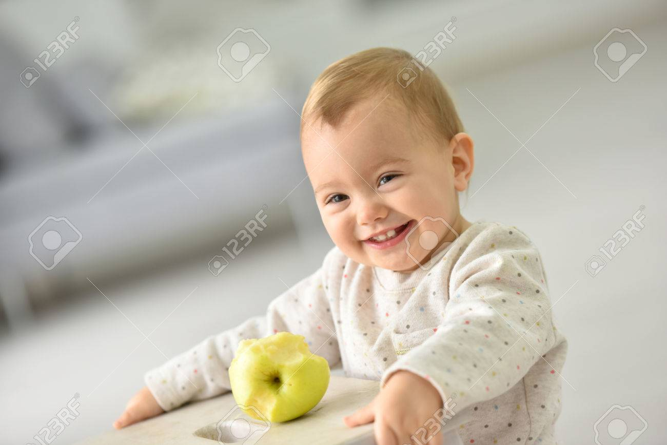 Cute 15-month-old baby girl eating an apple Stock Photo - 47872922